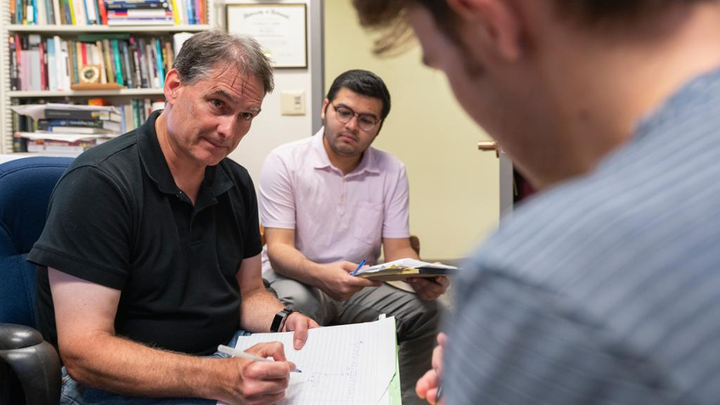 Professor meeting with two students in his office.