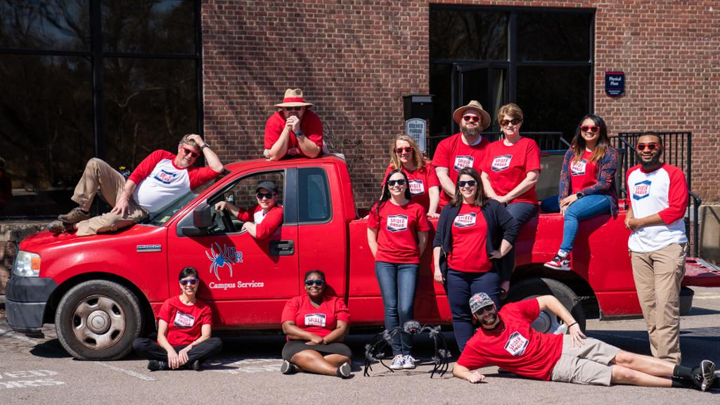 University staff members in matching red shirts posing in front of a red university truck.