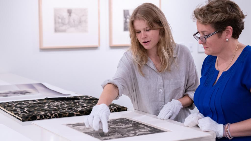 Student handling artwork in the University museum with a curator wearing gloves.