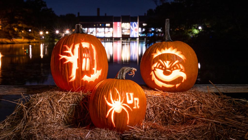 Carved jack-o-lanterns lit up at night with the lake in the background.