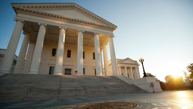 Exterior view of the Virginia Capitol building with the sun shining from behind.