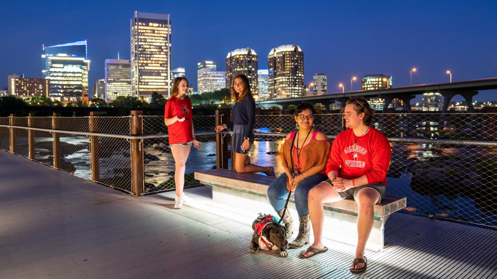 Four students socializing on a foot bridge over the James River with the Richmond city skyline behind them.