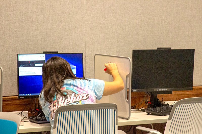A student writes on a mobile whiteboard in Gottwald E100
