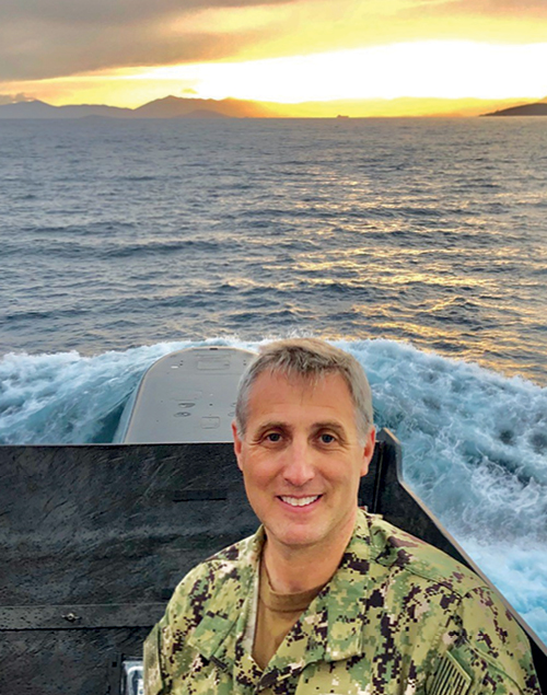 A photograph of Andy Burcher on the back of a submarine with the ocean and sunset behind him.