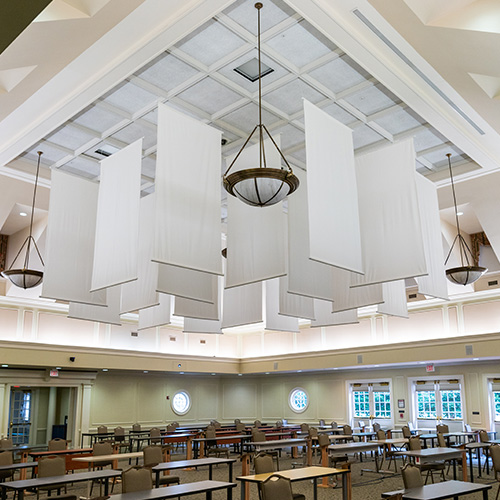 The ceiling of a large room in the Jepson Alumni Center that has been converted into a classroom. There are large rectangular white fabric panels hanging from the ceiling to help dampen sound to make the room more acoustically friendly as a teaching space.