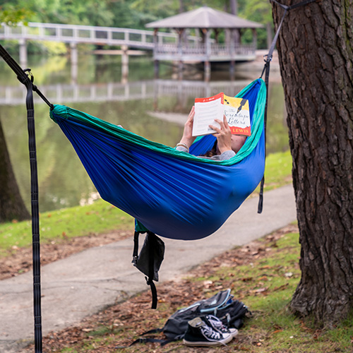 A person in a colorful hammock, reading a book, next to Westhampton Lake, with the gazebo in the background