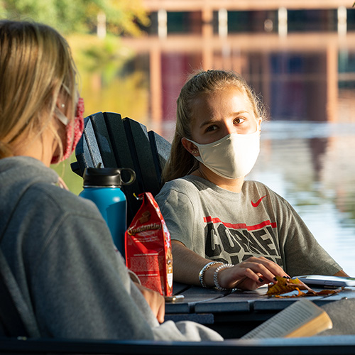 Two young blond women wearing cloth masks sit in Adirondack chairs by Westhampton Lake, with the Tyler Haynes Commons in the background