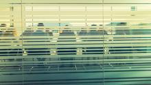 People in a boardroom behind frosted glass