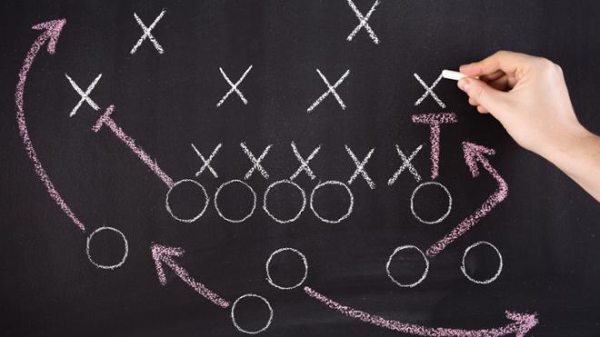 Football play drawn on chalkboard with Xs and Os