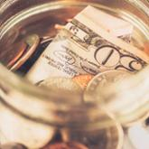 Mason jar filled with dollar bills and coins