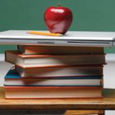 Apple atop stack of books and laptop in classroom
