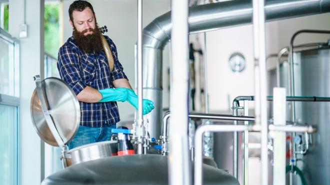 man amid brewing equipment