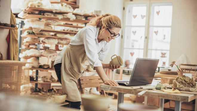 woman standing over laptop in pottery studio