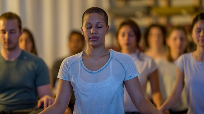 woman meditating among others in class