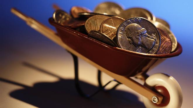 tiny wheelbarrow filled with coins