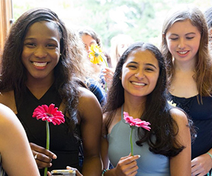 multicultural students smiling and holding flowers