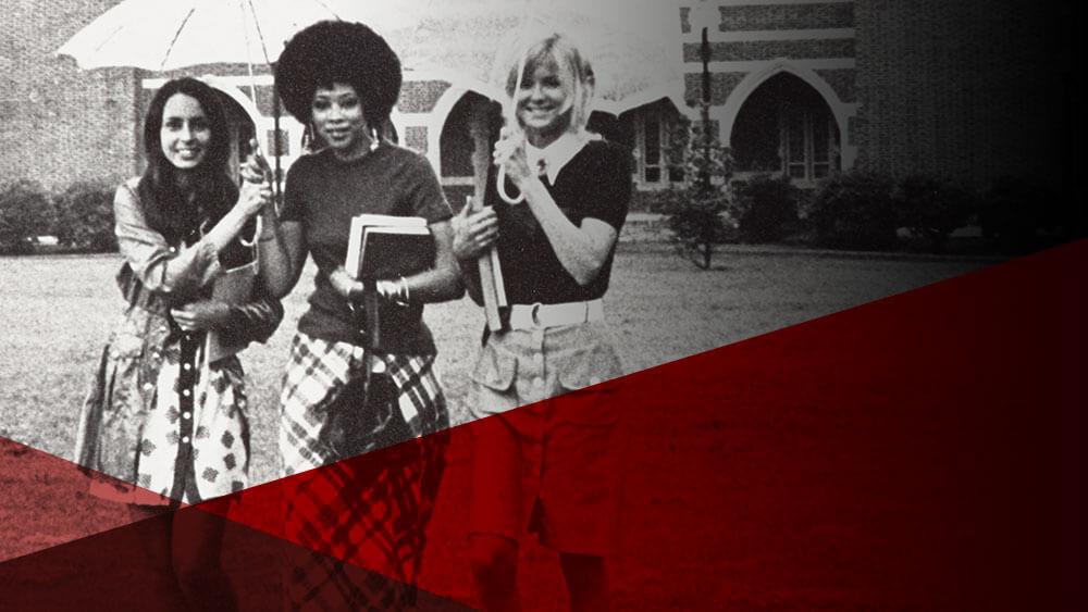 Three female students walking across campus